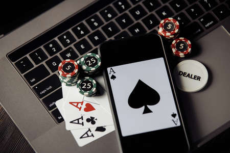 Stack of сhips, smartphone and playing cards on keaboard. Top view. Online casino concept
