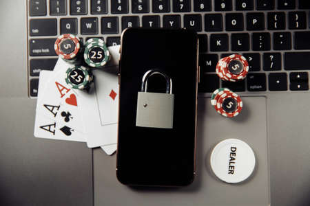 Law and rules for online gambling concept, smartphone with padlock and playing chips on keyboard