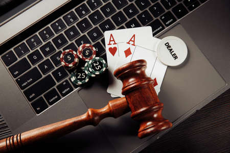 Gambling and law concept. Playing chips, aces and wooden gavel on keyboard 스톡 콘텐츠
