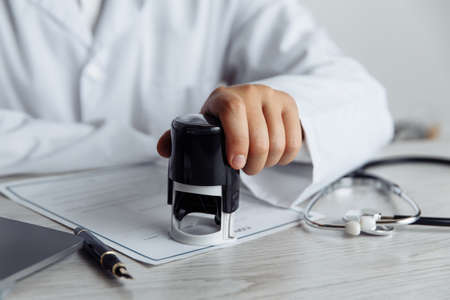 Male doctor in public medical office is stamping medical document. Healthcare concept 스톡 콘텐츠