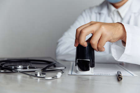 Male doctor in office is stamping medical document, close-up hand. Medicine concept