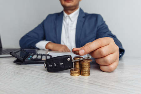 Black car key with contract on wooden table and man with money. Concept business finance and insurance, savings plans for car 스톡 콘텐츠