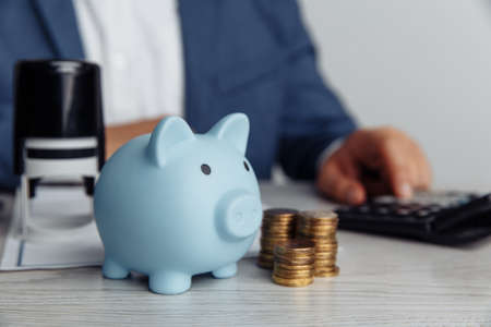 Piggy bank and coins on desk in office. Save money and management financial concept