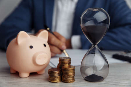 Businessman approves important contract in office. Pink piggy bank with stack of coins and hourglass on desk. Time is money 스톡 콘텐츠