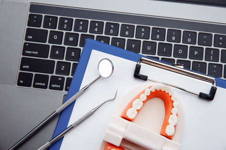 Healthy tooth model with dental tool on white table in dentists office. Teeth hygiene concept