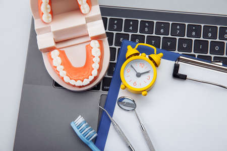 Healthy tooth model with dental tool and alarm clock in dentists office. Professional teeth hygiene concept