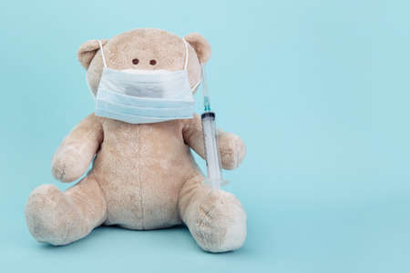 Stuffed Bear animal in mask with syringe isolated on blue. Pediatrician concept 스톡 콘텐츠