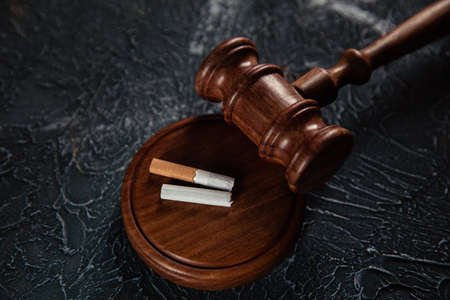 Wooden judge gavel and broken cigarette on grey background. Tobacco law