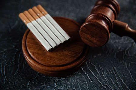 Wooden gavel and five cigarettes on grey table. Tobacco law