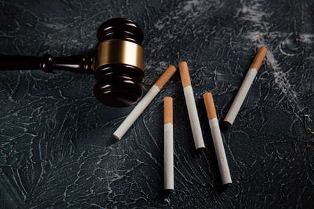 Wooden judge gavel and five cigarettes on grey table. Tobacco law 스톡 콘텐츠