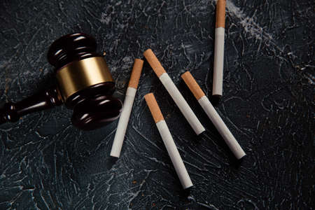 Judge gavel and cigarettes on grey background. Tobacco law