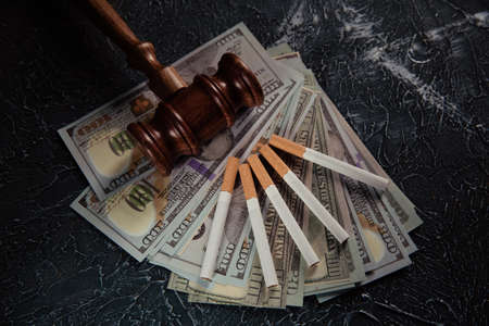 Judge gavel, money banknotes and cigarettes on grey table. Tobacco law