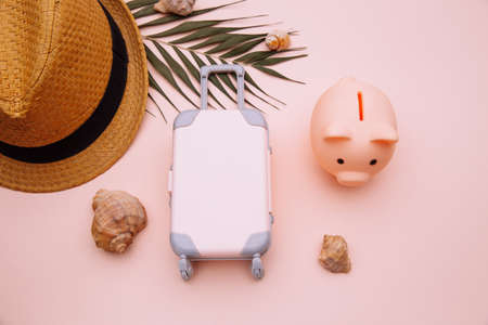Travel luggage suitcase with piggy bank on pink table with accessories close-up