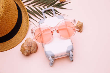 Pink suitcase and summer accessories on pink background close-up. Travel, summer vacation or tourism concept 스톡 콘텐츠