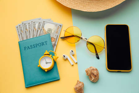 Concept of tourism. Travel accessories and passport with money on yellow blue background