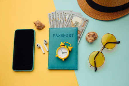 Outfit and accessories of traveler on yellow blue background. Travel concept. Overhead view of travelers accessories