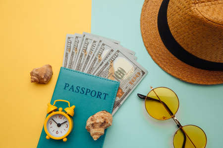 Vacation travel adventure trip concept. Minimal simple flat lay with hat, passport and shell on yellow blue background. Tourist essentials Stock fotó