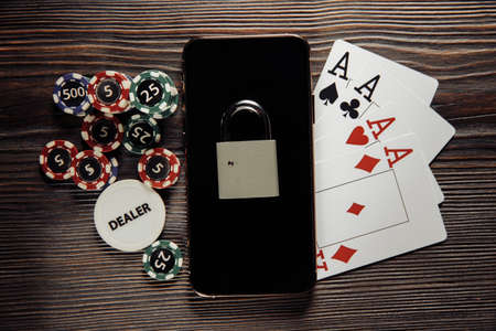 Smartphone with padlock, poker chips and playing cards. Concept of Law and regulation of gambling Stock Photo