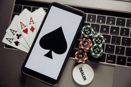 Online poker casino theme. Gambling chips, smartphone and playing cards on laptop keyboard