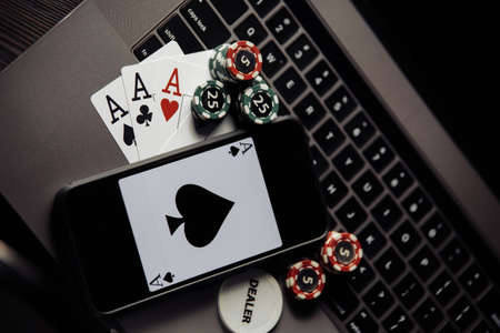 Poker chips, cards and smartphone on a grey keyboard. Poker online concept