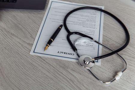Modern doctors office desk. Stethoscope and healthcare contract on wooden table Фото со стока