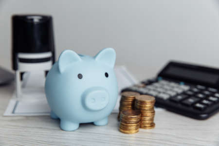 Blue piggy bank, stamp and coins on wooden desk in office. Save money and management financial concept 写真素材