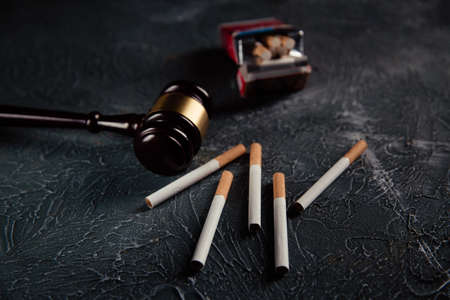 Judge gavel and five cigarettes on grey table. Tobacco law