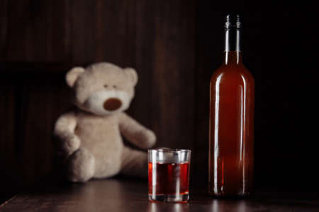 Child abuse concept. Teddy bear as a symbol of childs safety and bottle with glass on a wooden table