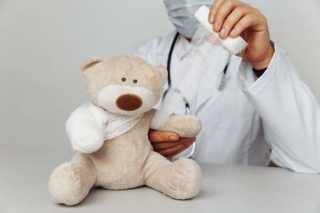 Pediatrician in mask bandage teddy bear in medical office. Children healthcare concept