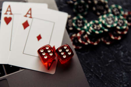Chips, red dices and playing cards with aces for poker online or casino gambling on laptop keyboard close-up. Online casino concept