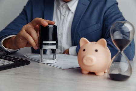 Businessman approves important contract. Piggy bank with stack of coins and hourglass on desk close-up. Time is money concept Banco de Imagens