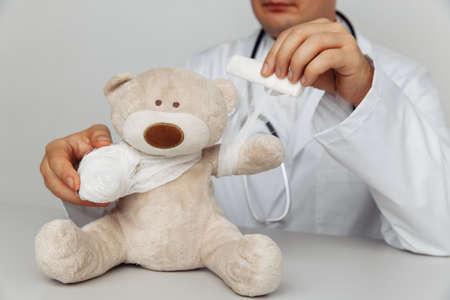 Pediatrician bandage teddy bear in medical office. Children healthcare concept