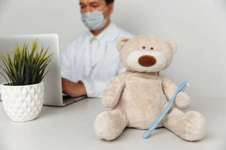 Teddy Bear with toothbrush at dentists office. Child healtcare and treatment concept