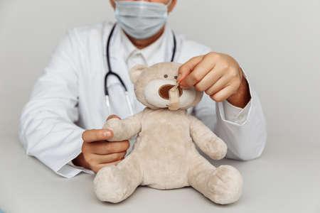 Kind pediatrician in mask treats teddy bear. Child healtcare and treatment concept