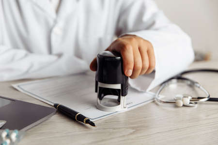 Male doctor in public medical office is stamping medical document. Healthcare and medicine concept Banque d'images