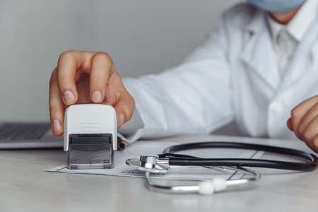 Male doctor in public medical office is stamping medical document. Medicine and healthcare concept