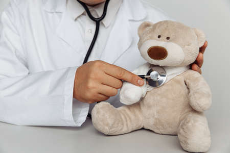 Doctor with stethoscope and teddy bear in medical office. Children healthcare concept