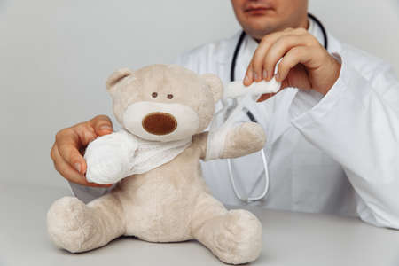 Serious pediatrician bandage teddy bear in medical office. Children healthcare concept