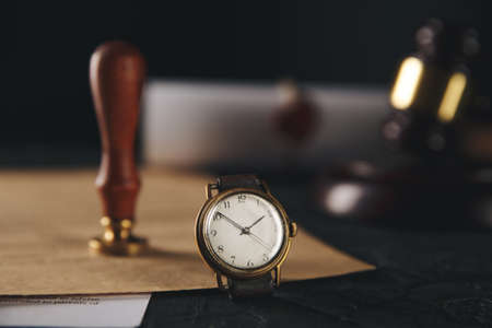 Notary stamp and wooden gavel with watch on the table.