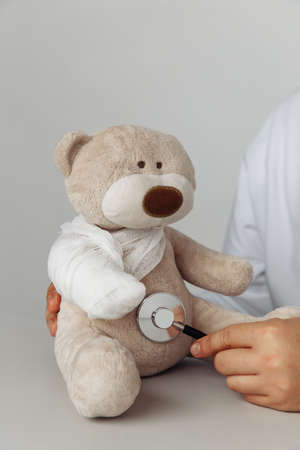 Pediatrician concept. Doctors hand with stethoscope and teddy bear in medical office