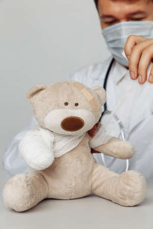 Pediatrician in mask bandage teddy bear in medical office. Close-up. Vertical image. Children healthcare concept