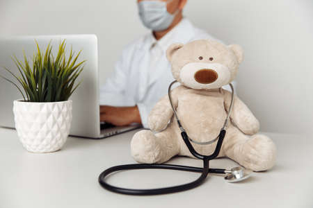 Teddy Bear with stethoscope in pediatrician office. Child healtcare concept