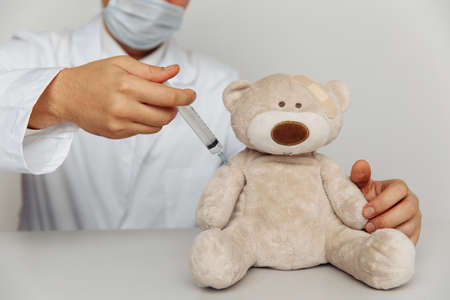 Male pediatrician makes an injection for sick teddy bear. Child healtcare and treatment concept