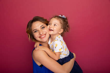 Mother holding little daughter on the hands and smiling standing in a bright studio.