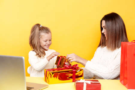 Handsome mother with little daughter unpaking gifts sitting isolated over the yellow background. 版權商用圖片
