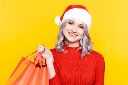 Santa girl in the hat holding big bags with presents isolated in the yellow studio. Stock Photo