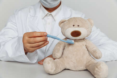 Dentist in mask cleaning teeth of teddy bear. Children dentist concept