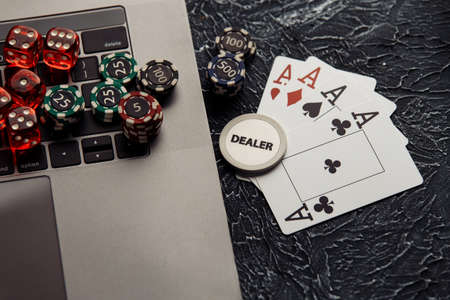 Online casino concept. Gambling chips, cards and dices on laptop keyboard