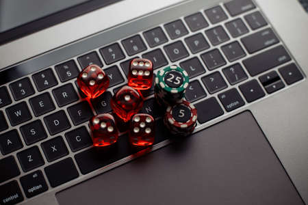 Online casino theme. Gambling chips and five red dices on laptop keyboard. Top view 免版税图像
