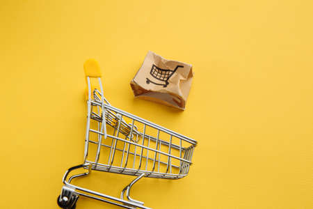 Damaged paper box and shopping cart on a yellow background. Delivery concept. Shipment accident